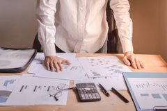 Επιχειρηματίας που στέκεται στην αρχή με τα έγγραφα που τοποθετούνται στον πίνακα Ανησυχίες και επιχειρησιακός προγραμματισμός στοκ εικόνες