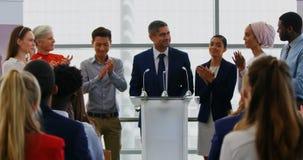 Επιχειρηματίας που στέκεται στην εξέδρα με τους συναδέλφους του στο επιχειρησιακό σεμινάριο 4k φιλμ μικρού μήκους