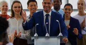 Επιχειρηματίας που στέκεται στην εξέδρα με τους συναδέλφους του στο επιχειρησιακό σεμινάριο 4k απόθεμα βίντεο