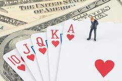 επιχειρηματίας που στέκεται στην κάρτα τυχερού παιχνιδιού με το αμερικανικό δολάριο Στοκ εικόνα με δικαίωμα ελεύθερης χρήσης