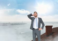 Επιχειρηματίας που στέκεται στη στέγη με το θαλάσσιο λιμένα καπνοδόχων και πόλεων Στοκ Εικόνα