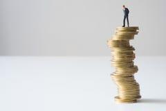 Επιχειρηματίας που στέκεται στον επικίνδυνο σωρό νομισμάτων Στοκ Εικόνα