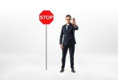 Επιχειρηματίας που στέκεται στο άσπρο υπόβαθρο που κάνει τη χειρονομία χεριών στάσεων με το σημάδι κυκλοφορίας εκτός από τον Στοκ Εικόνες