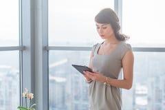 Επιχειρηματίας που στέκεται στο ελαφρύ δωμάτιο σοφιτών, δακτυλογραφώντας, διαβάζοντας το ηλεκτρονικό ταχυδρομείο, κοιτάζοντας βια στοκ εικόνες