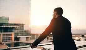 Επιχειρηματίας που στέκεται στο μπαλκόνι σαλονιών αερολιμένων και που φαίνεται outsi Στοκ εικόνα με δικαίωμα ελεύθερης χρήσης