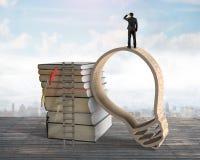 Επιχειρηματίας που στέκεται στο ξύλινο πλαίσιο μορφής lightbulb με τα βιβλία Στοκ φωτογραφίες με δικαίωμα ελεύθερης χρήσης