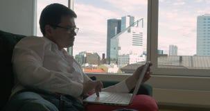 Επιχειρηματίας που στηρίζεται στον καναπέ με το lap-top απόθεμα βίντεο