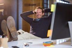 Επιχειρηματίας που στηρίζεται στο γραφείο υπολογιστών Στοκ Φωτογραφία