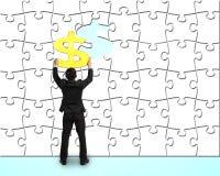 Επιχειρηματίας που συγκεντρώνει το χρυσό σύμβολο χρημάτων στον τοίχο γρίφων Στοκ Φωτογραφία
