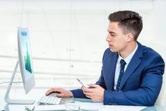 Επιχειρηματίας που συγχρονίζει το έξυπνο τηλέφωνο με τον υπολογιστή στοκ φωτογραφίες με δικαίωμα ελεύθερης χρήσης