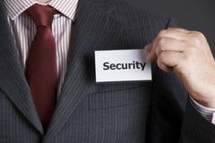 Επιχειρηματίας που συνδέει το διακριτικό ασφάλειας με το σακάκι στοκ εικόνα με δικαίωμα ελεύθερης χρήσης