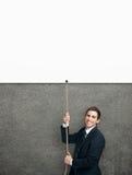 Επιχειρηματίας που συρρέει επάνω στη σειρά με την άσπρη αφίσα Στοκ εικόνες με δικαίωμα ελεύθερης χρήσης