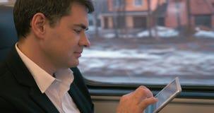 Επιχειρηματίας που ταξιδεύει με το τραίνο με το PC ταμπλετών απόθεμα βίντεο