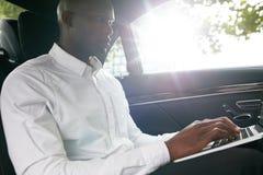 Επιχειρηματίας που ταξιδεύει στην εργασία σε ένα αυτοκίνητο που χρησιμοποιεί το lap-top Στοκ φωτογραφία με δικαίωμα ελεύθερης χρήσης
