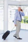 Επιχειρηματίας που τραβά τη βαλίτσα και που μιλά στο τηλέφωνο Στοκ εικόνες με δικαίωμα ελεύθερης χρήσης
