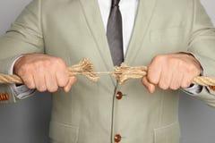 Επιχειρηματίας που τραβά το ξεφτισμένο σχοινί στις αντίθετες κατευθύνσεις στοκ φωτογραφίες με δικαίωμα ελεύθερης χρήσης