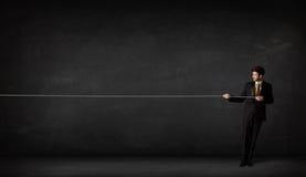Επιχειρηματίας που τραβά το σχοινί στο γκρίζο υπόβαθρο Στοκ φωτογραφία με δικαίωμα ελεύθερης χρήσης