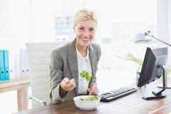 Επιχειρηματίας που τρώει τη σαλάτα στο γραφείο της Στοκ Φωτογραφία