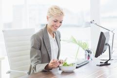 Επιχειρηματίας που τρώει τη σαλάτα στο γραφείο της Στοκ Φωτογραφίες