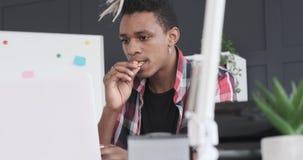 Επιχειρηματίας που τρώει το μπισκότο και που εργάζεται στο lap-top στο γραφείο φιλμ μικρού μήκους