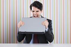 Επιχειρηματίας που τρώει το lap-top στοκ φωτογραφία