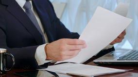 Επιχειρηματίας που υπογράφει τα έγγραφα με ένα φλιτζάνι του καφέ στον πίνακα απόθεμα βίντεο