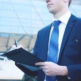 Επιχειρηματίας που υπογράφει τη σύμβαση εκθέσεων αποδοχής, σύγχρονο πολυόροφο κτίριο Στοκ φωτογραφία με δικαίωμα ελεύθερης χρήσης
