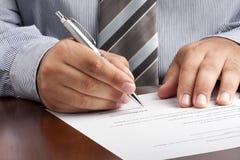 Επιχειρηματίας που υπογράφει το έγγραφο συμβάσεων στοκ εικόνα