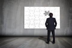 Επιχειρηματίας που υπολογίζει τα κομμάτια γρίφων Στοκ Εικόνα