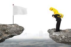 Επιχειρηματίας που φέρνει το τρισδιάστατο χρυσό σημάδι δολαρίων στον απότομο βράχο με το cloudscap Στοκ Φωτογραφίες