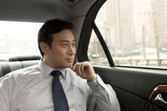 Επιχειρηματίας που φαίνεται έξω παράθυρο αυτοκινήτων Στοκ Εικόνα