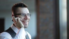 Επιχειρηματίας που φαίνεται έξω το παράθυρό του που μιλά στο τηλέφωνο στο γραφείο του απόθεμα βίντεο