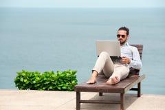 Επιχειρηματίας που φορά ένα κοστούμι που χρησιμοποιεί το lap-top στην παραλία Στοκ φωτογραφία με δικαίωμα ελεύθερης χρήσης