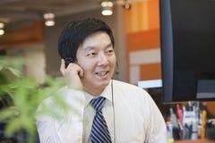 Επιχειρηματίας που φορά την κάσκα στο γραφείο και την ομιλία Στοκ Εικόνες