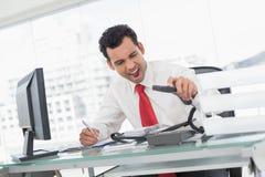 Επιχειρηματίας που φωνάζει δεδομένου ότι διοργανώνει το τηλέφωνο στο γραφείο Στοκ εικόνα με δικαίωμα ελεύθερης χρήσης