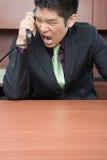 Επιχειρηματίας που φωνάζει κάτω από το τηλέφωνο Στοκ Φωτογραφία