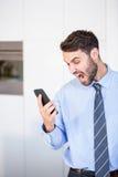 Επιχειρηματίας που φωνάζει κοιτάζοντας στο κινητό τηλέφωνο Στοκ Φωτογραφία
