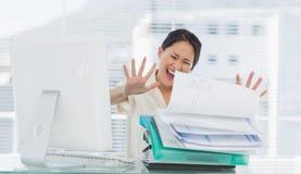 Επιχειρηματίας που φωνάζει με το σωρό των φακέλλων στο γραφείο Στοκ εικόνα με δικαίωμα ελεύθερης χρήσης
