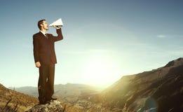 Επιχειρηματίας που φωνάζει στην κορυφή της έννοιας βουνών Στοκ εικόνες με δικαίωμα ελεύθερης χρήσης