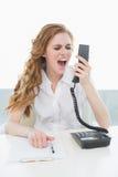 Επιχειρηματίας που φωνάζει στο τηλέφωνο στο γραφείο Στοκ εικόνες με δικαίωμα ελεύθερης χρήσης