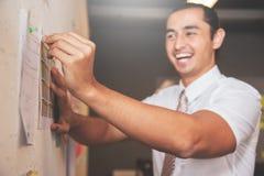 Επιχειρηματίας που χαμογελά και που καταρτίζει τα έγγραφα σχετικά με τον τοίχο για τη συνεδρίαση Στοκ φωτογραφία με δικαίωμα ελεύθερης χρήσης