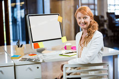 Επιχειρηματίας που χαμογελά καθμένος από το γραφείο υπολογιστών Στοκ Φωτογραφία