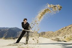Επιχειρηματίας που χρησιμοποιεί ένα φτυάρι στην έρημο Στοκ εικόνα με δικαίωμα ελεύθερης χρήσης