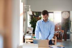 Επιχειρηματίας που χρησιμοποιεί ένα lap-top για την επιχείρηση σε ένα γραφείο Στοκ Εικόνες