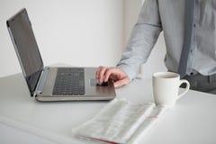 Επιχειρηματίας που χρησιμοποιεί ένα lap-top με ένα φλυτζάνι του τσαγιού Στοκ Φωτογραφία