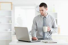 Επιχειρηματίας που χρησιμοποιεί ένα lap-top πίνοντας τον καφέ Στοκ φωτογραφία με δικαίωμα ελεύθερης χρήσης