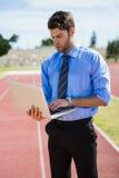 Επιχειρηματίας που χρησιμοποιεί ένα lap-top στην τρέχοντας διαδρομή Στοκ Εικόνες