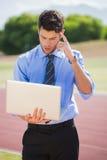 Επιχειρηματίας που χρησιμοποιεί ένα lap-top στην τρέχοντας διαδρομή Στοκ Εικόνα