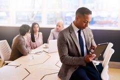 Επιχειρηματίας που χρησιμοποιεί μια ταμπλέτα τρεις συναδέλφους που κάθονται με πίσω από τον Στοκ Φωτογραφία