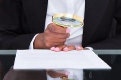 Επιχειρηματίας που χρησιμοποιεί την ενίσχυση - γυαλί για να διαβάσει το έγγραφο στο γραφείο Στοκ Φωτογραφία